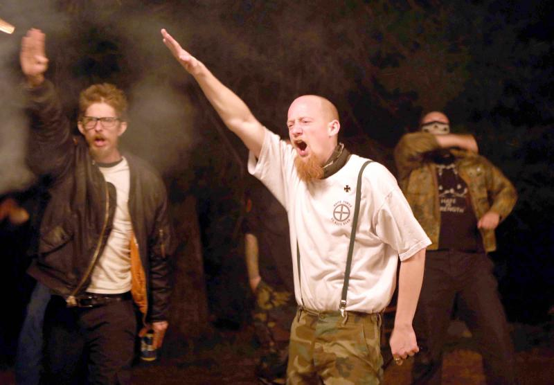 Members-of-the-ShieldWall-Network-a-white-nationalist-group-perform-a-Nazi-salute-as-a-swastika-and-cross-burn-during-a-party-outside-Atkins-Arkansas-U.S.-March-9-2019.-REUTERS